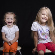 Portrait of two young girls sitting on chairs — Stock Photo