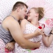 A young man gives a ring girl lying in bed — Stock Photo
