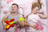 The couple in the bed-husband plays the guitar, the wife sleeps — Stock Photo