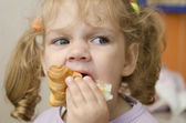 The little girl with enthusiasm and eats a roll with pleasure — Stock Photo