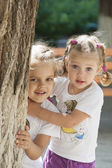 Two children peep out from behind a tree — Stock Photo