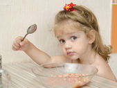 The child with the inquiring views eats porridge — Zdjęcie stockowe