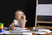Girl-architect sitting behind a Desk and thought dreamily — Stock Photo
