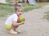 Little girl sitting on his haunches with a ball on the Playground — Stock Photo