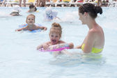 A mother and two daughters are swimming in a public pool — Stock Photo