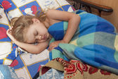 A child of four years sleep in a bed with an old sheets and blankets — Stock Photo