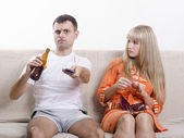 The pair on the couch. He looks drinking beer, she looks at him reproachfully — Stock Photo