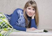 девушка, читающая книгу под одеялом на диване — Стоковое фото