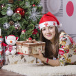 Girl with a new year gift lies near the Christmas tree — Foto Stock