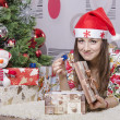 Girl disappointed a little gift, lying near the Christmas tree — Stock Photo #37162107