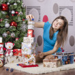 Girl near a Christmas tree collects from gifts pyramid — 图库照片