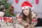 The girl took out a large box of little boxes with a gift, lies near the Christmas tree — Stock Photo