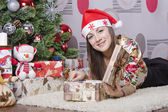 Girl opens the box with a new year gift and lies near the Christmas tree — Stock Photo