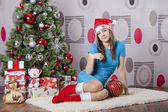 Girl with a large Christmas tree ball is sitting by the Christmas tree — Stock Photo