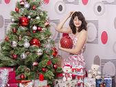 A girl knows where to hang on the Christmas tree big red ball — Foto de Stock