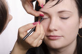 Makeup artist in the process of makeup colors eyelashes model — Stock Photo