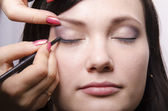 Makeup artist in the process of makeup colors upper eyelids model — Stock Photo