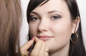 Makeup artist in the process of make-up, lipstick model — Stock Photo
