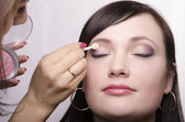 Makeup artist in the process of makeup colors upper eyelids model — Foto de Stock