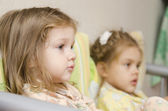 Two children sit on couch and look to right — Stock Photo