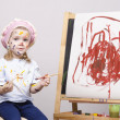 Photo: Portrait of girl artist at easel