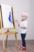 Girl artist paints on canvas — Stock Photo