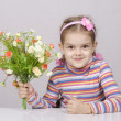 Stock Photo: Girl with bouquet of flowers sitting at table