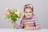 Girl with a bouquet of flowers sitting at table — Stockfoto
