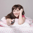 Girl with remote control in bed watching TV — Stock Photo
