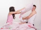 Ungt par i sängen ordnade en kudde kamp — Stockfoto