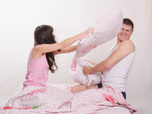 Young couple in bed arranged a pillow fight — Stockfoto