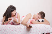 Wife looks at her husband sleeping football fan — Stock Photo