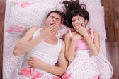 Young couple in bed morning yawning — Stock Photo