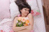 Girl in bed hugged a bouquet of roses — Stock Photo