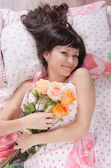 Beautiful young girl lying in bed with bouquet of roses — Stock Photo