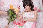 Sleeping girl presented with a bouquet of roses — Stock Photo