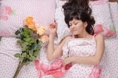 Girl gave flowers in bed — Stock Photo