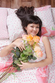 Beautiful young girl lying in bed with flowers — Stock Photo