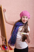 Twelve year old girl paints on an easel — Stock Photo