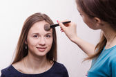 Makeup artist gets fluffy powder brush on forehead model — Stock Photo