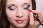 Drawing bright shadows on girl's eyelids with makeup — Stock Photo