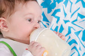 Baby drinking milk formula from a bottle — Stock Photo