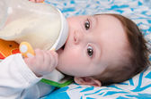 Baby drinking milk from a bottle — Stock Photo
