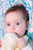 Six-month girl drinks milk from a bottle — Stock Photo
