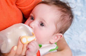 Six month old baby drinking milk from a bottle — Stock Photo