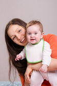 Young happy mother hugging baby girl in bib — Stock Photo