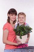 Mom and daughter with a potted flower in hands — 图库照片