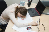 Tired woman asleep on a workplace at office — Stock Photo
