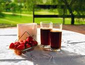 Zwei Gläser Coda-Drink und ein Stapel der Erdbeeren auf den Tisch an einem sonnigen Tag — Stockfoto