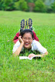 Young asian woman lie down on grass with book — Stock Photo